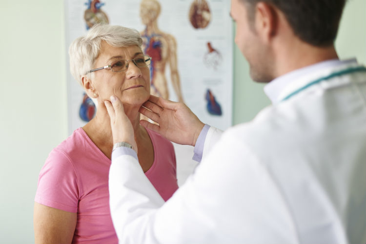 Senior woman getting her thyroid checked by doctor