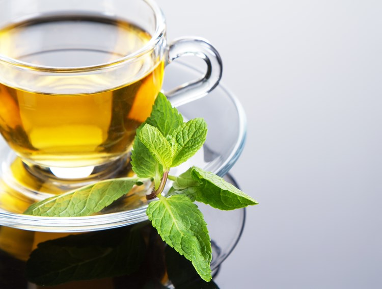 A cup of hot tea with a mint leaf beside it