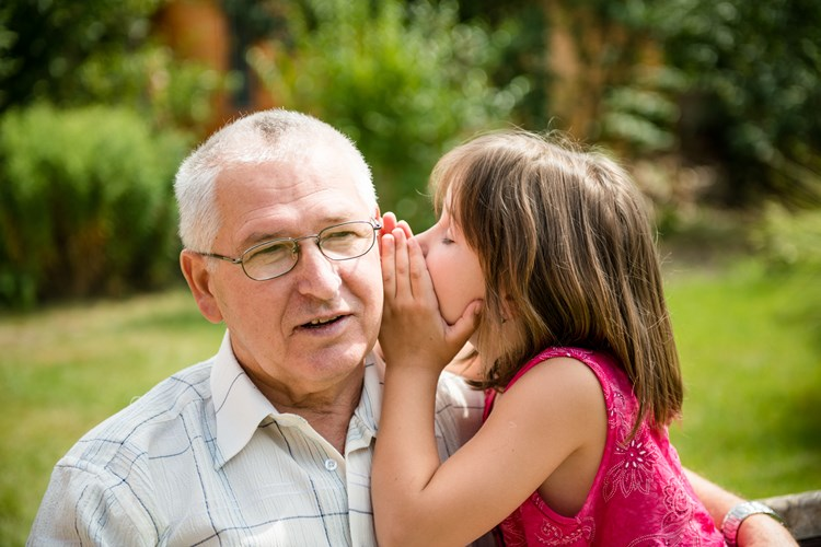 Young girl whispering into her grandfather's ear