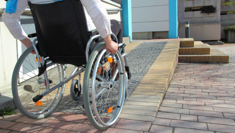 Woman in a wheelchair rolling up a ramp to her front door