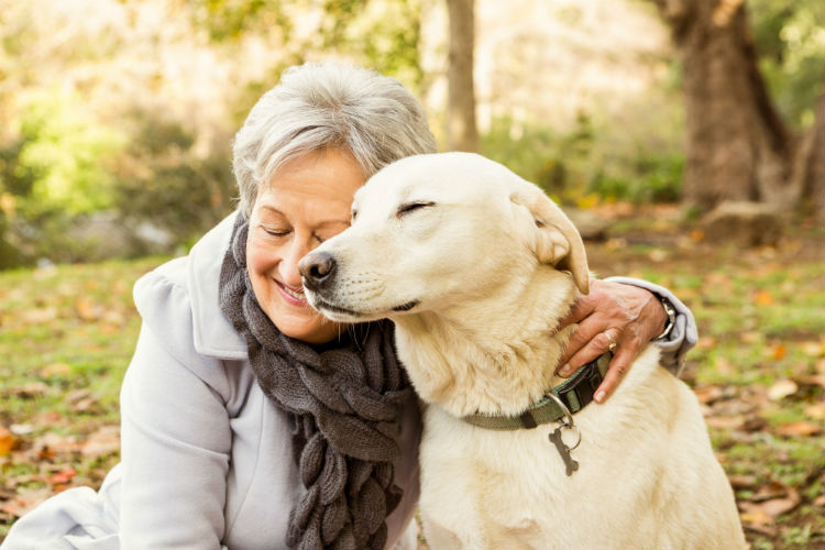 Senior woman smiling and embracing her dog with a hug