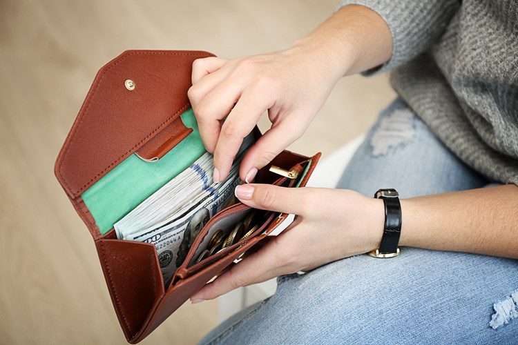 A person reaching into their open wallet showing cash,coins, and cards inside