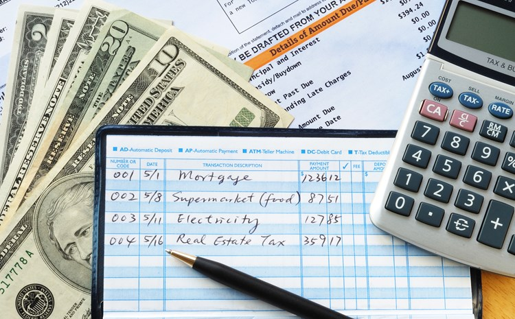 A close up of an open checkbook, calculator, cash, and bills spread out across a desk