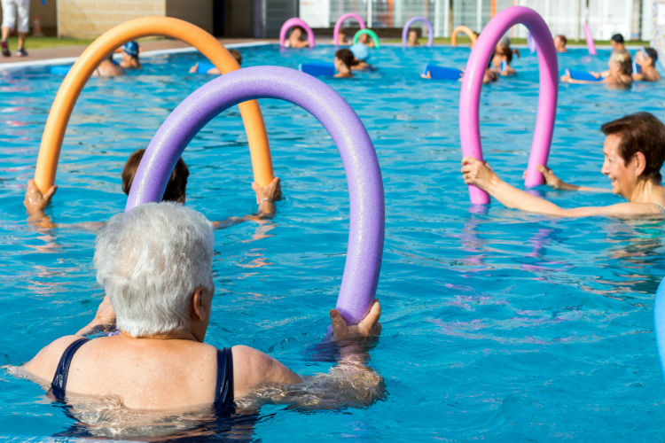 Elderly women exercising in pool with noodles