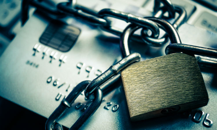 A padlock and chains surrounding a credit card for protection