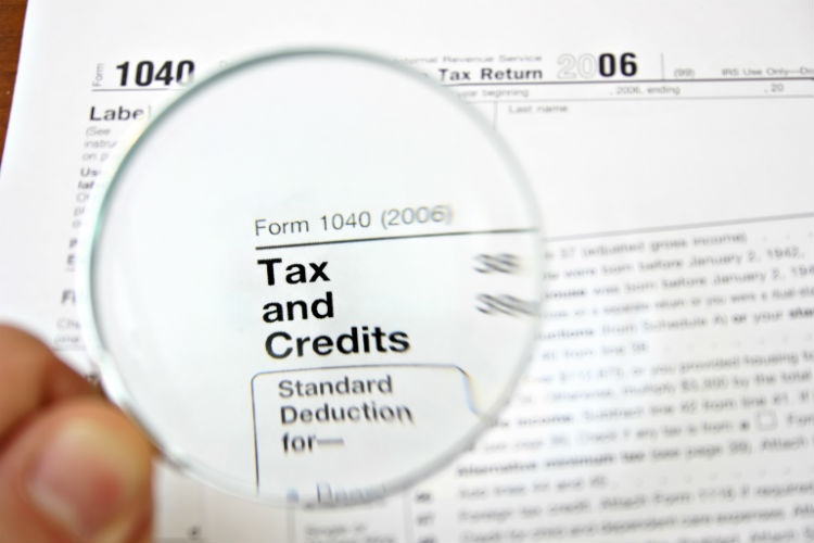 Magnifying glass over tax and credit paper