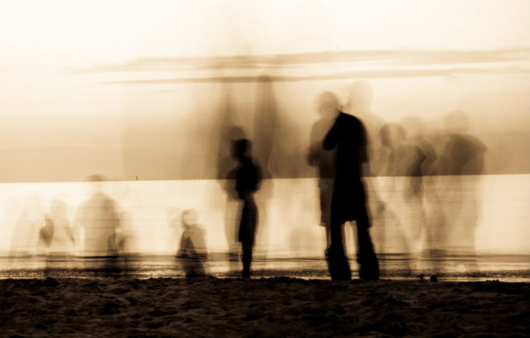 Blurred image of people standing on beach