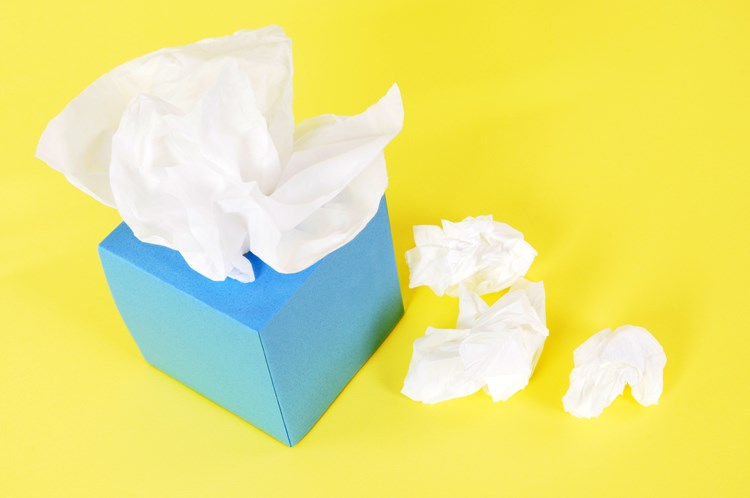 A box of tissues and crumpled tissues used to dry tears laying next to it