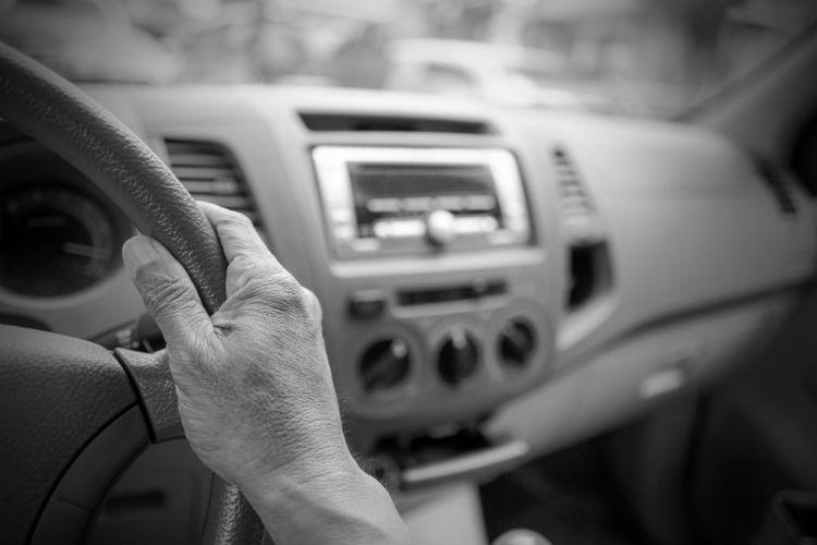 Close up of senior man's hand on steering wheel