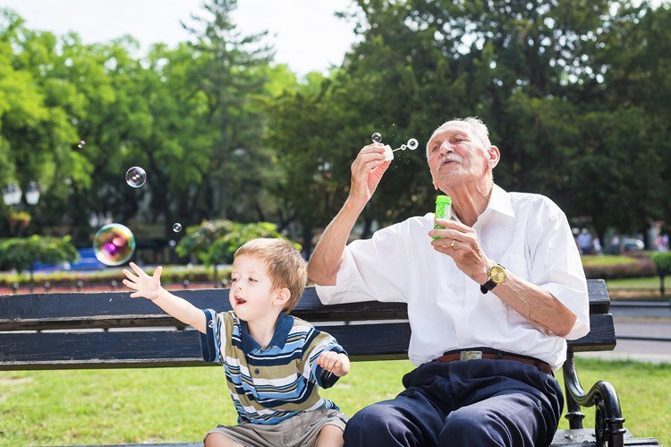 A grandfather blowing bubbles for his grandson to chase