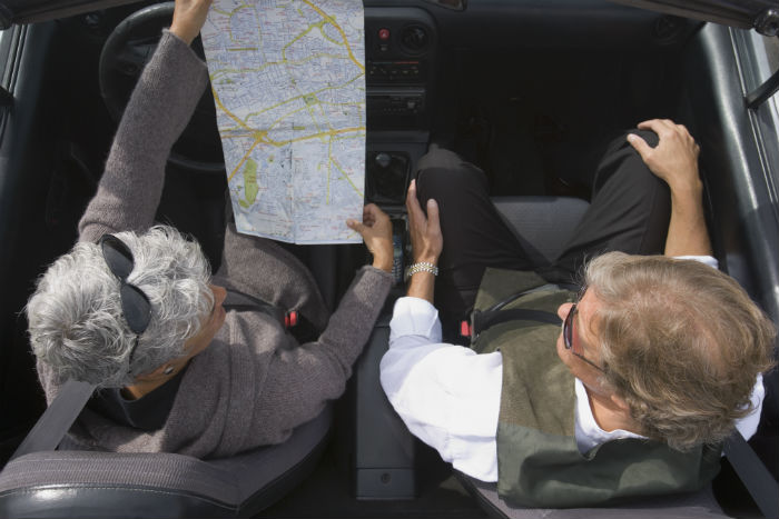 Senior couple looking at a map in their car
