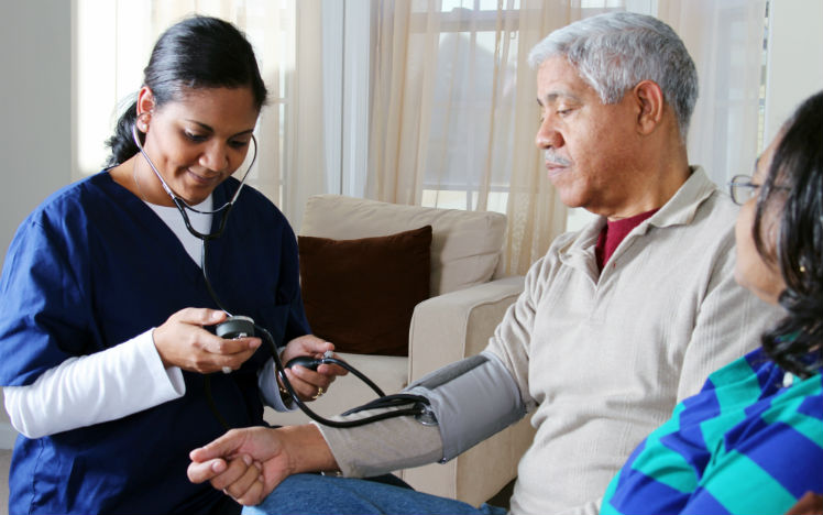 A home care nurse checking a senior man's vital signs