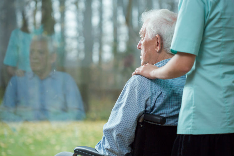Elderly man in wheelchair looking out window