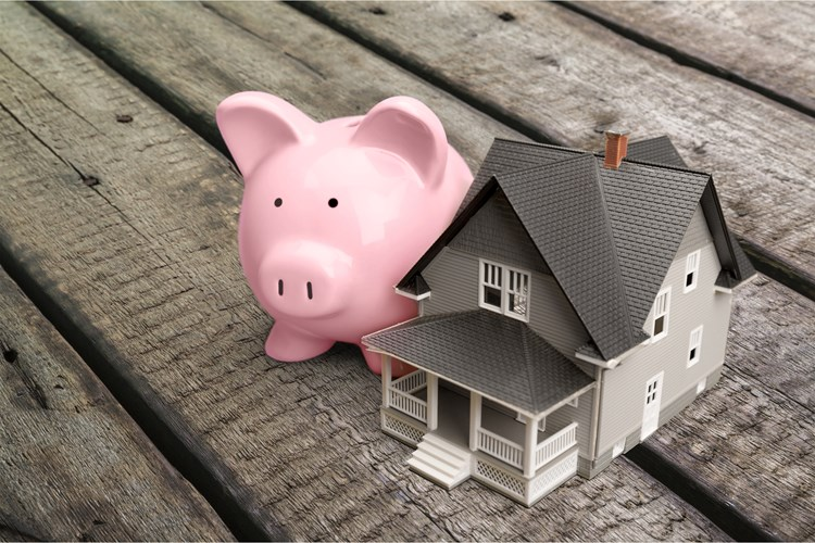 A piggy bank standing next to a house