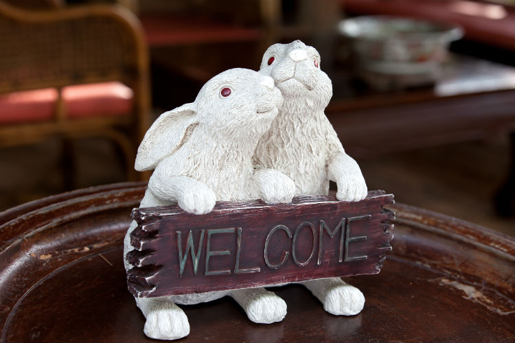 Two bunny figurines holding welcome sign