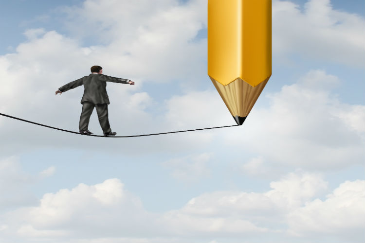 A man balancing on a thin line being drawn in the clouds by a large pencil