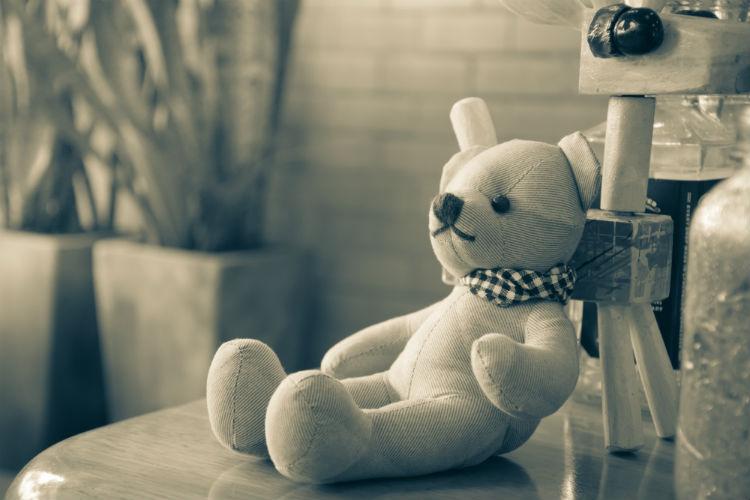 Teddy bear sitting on nightstand