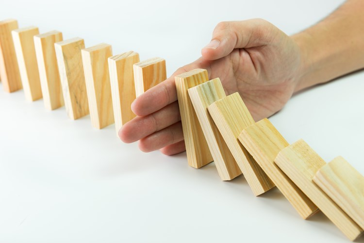 Hand preventing domino blocks from falling over