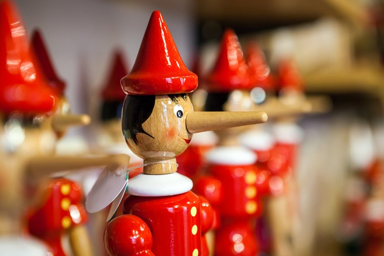 A close up of a wooden Pinocchio doll with a long nose