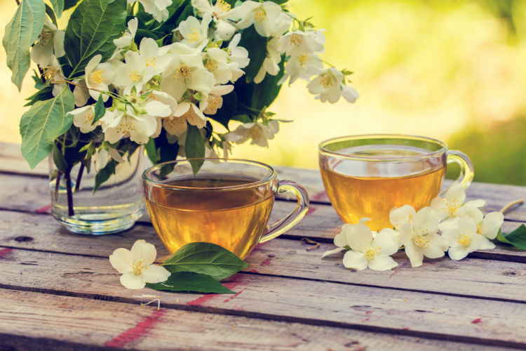 Two tea cups on an outdoor table with flowers