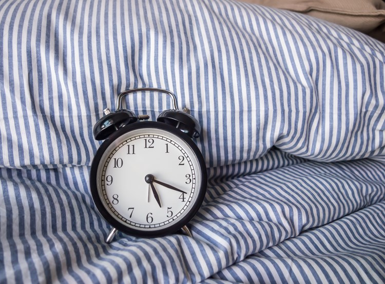An alarm clock resting on a pillow in an unmade bed