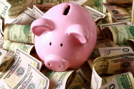 A piggy bank surrounded by a pile of money