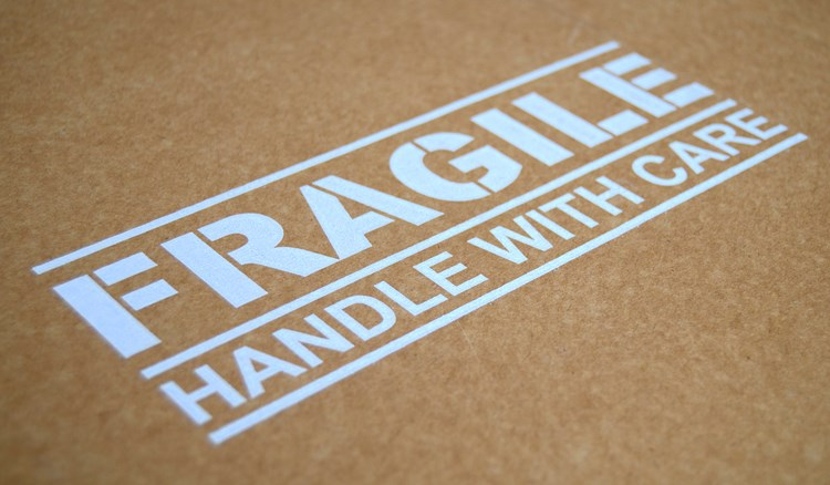 "Text that reads""fragile handle with care"" stamped on top of a package"