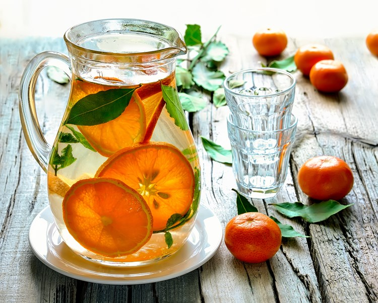 A pitcher of water with slices of orange inside and two empty glasses next to it