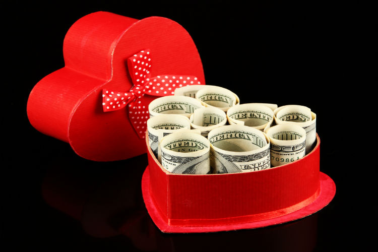 One hundred-dollar bills rolled up into a heart shaped chocolate box