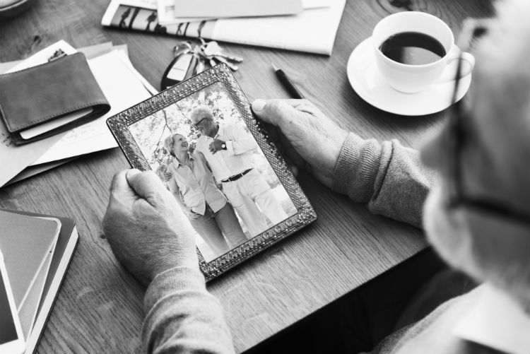 Elderly man holding a photo of him and his wife