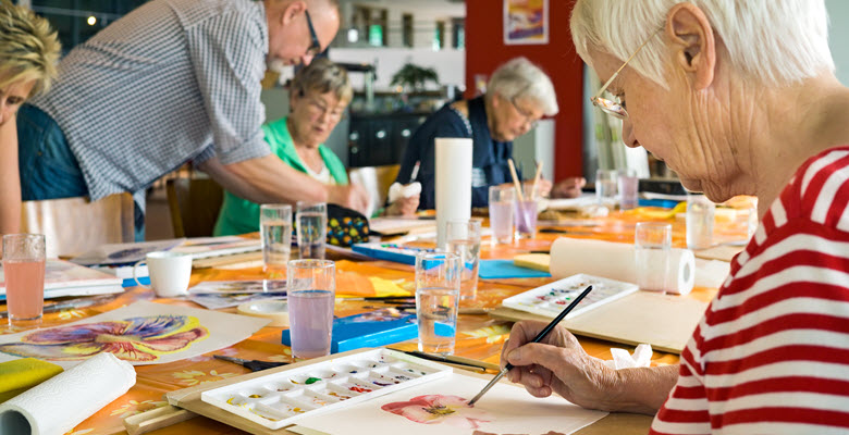 A group of seniors enjoying a painting class