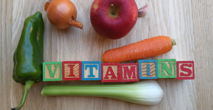 "A selection of vegetable with alphabet blocks that spell ""vitamins"""