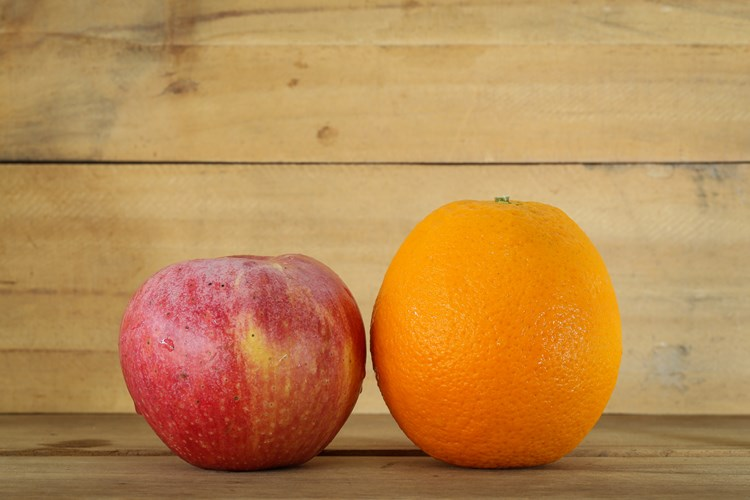 An apple and orange placed next to each other for comparison