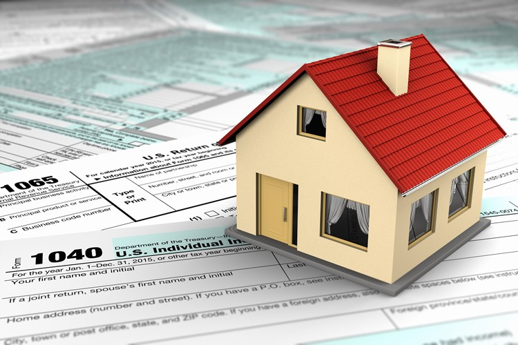 Small house resting on top of estate tax forms