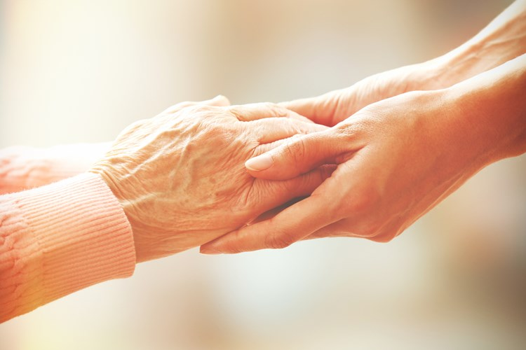 A caregiver holding the hands of a Parkinson's patient offering support