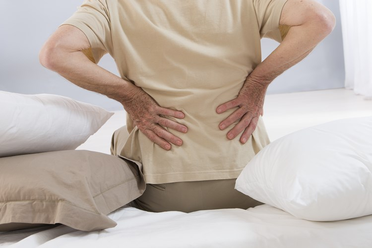 Elderly man holding his back due to arthritis pain