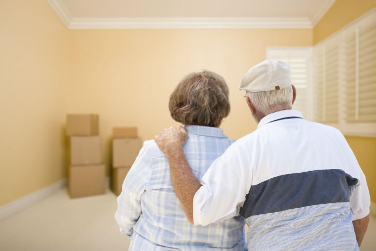 A senior couple staring at an empty room with moving boxes in the corner