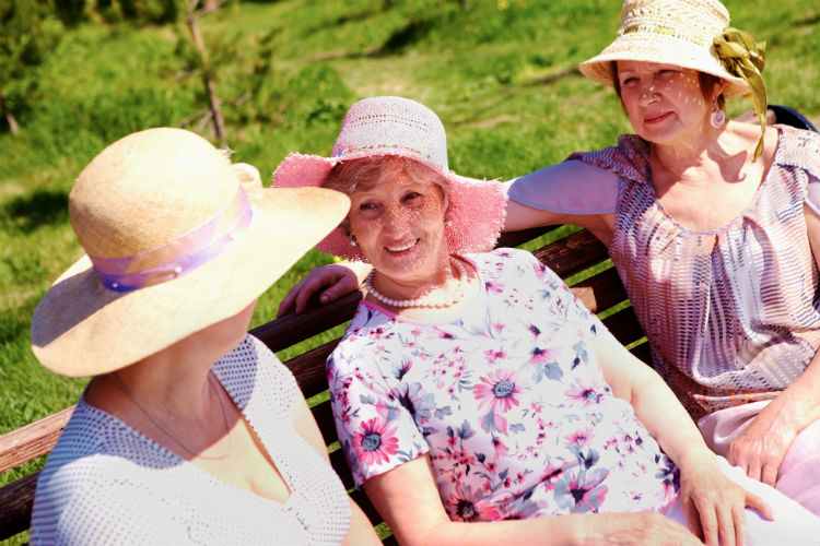 three women talking on a bench