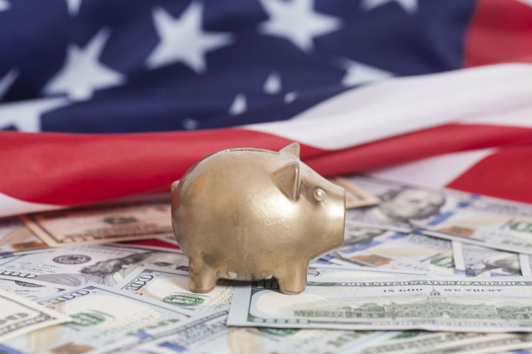 Tiny gold piggy bank in center on top of money and American flag in the background