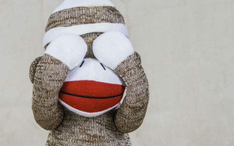 A sock monkey covering its eyes