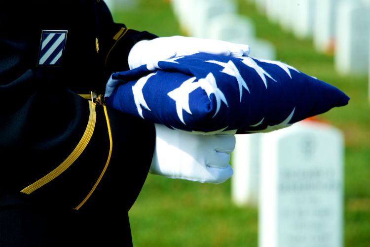 Veteran holding a flag in preparation for a burial