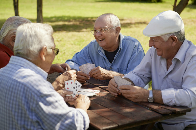 Active retired seniors enjoying a game of cards on a picnic table