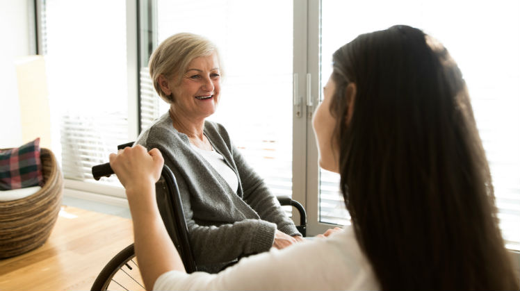 Senior woman in wheelchair smiling at her caregiver