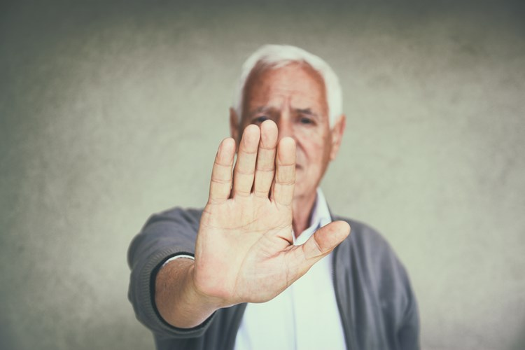 Elderly man raising his hand in front of him to refuse help