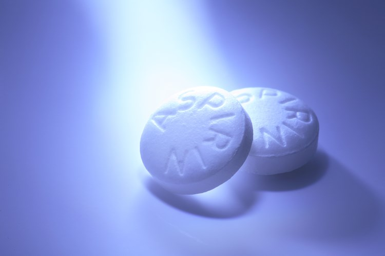 A light shining on two aspirin pills