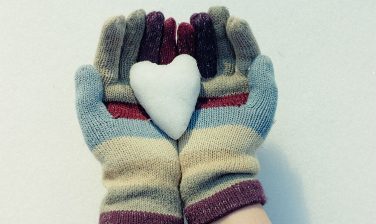 Two gloved hands holding a heart made of snow