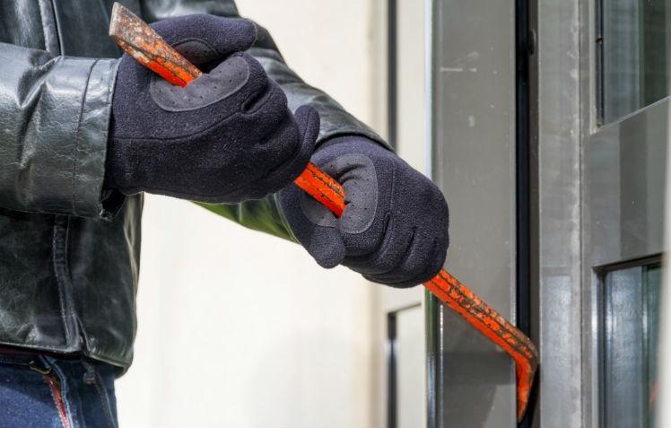 A burglar using an orange crowbar to pry open a door