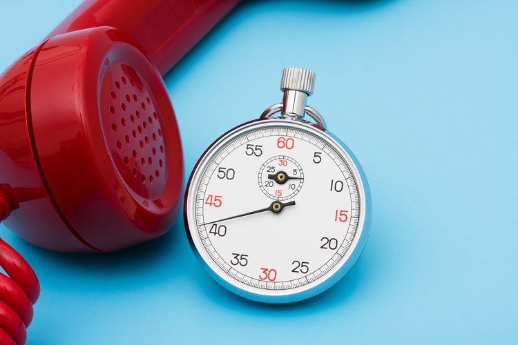 A stopwatch resting next to a red phone that is off the hook