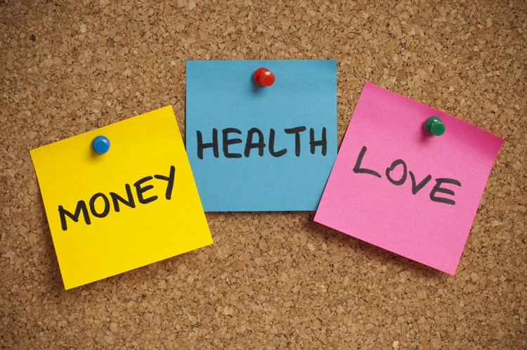 Three post it notes pinned on a billboard that read money health love