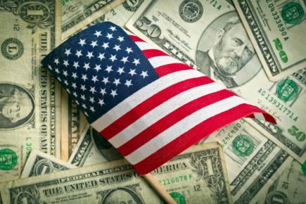 Top view of American flag with US dollars in background